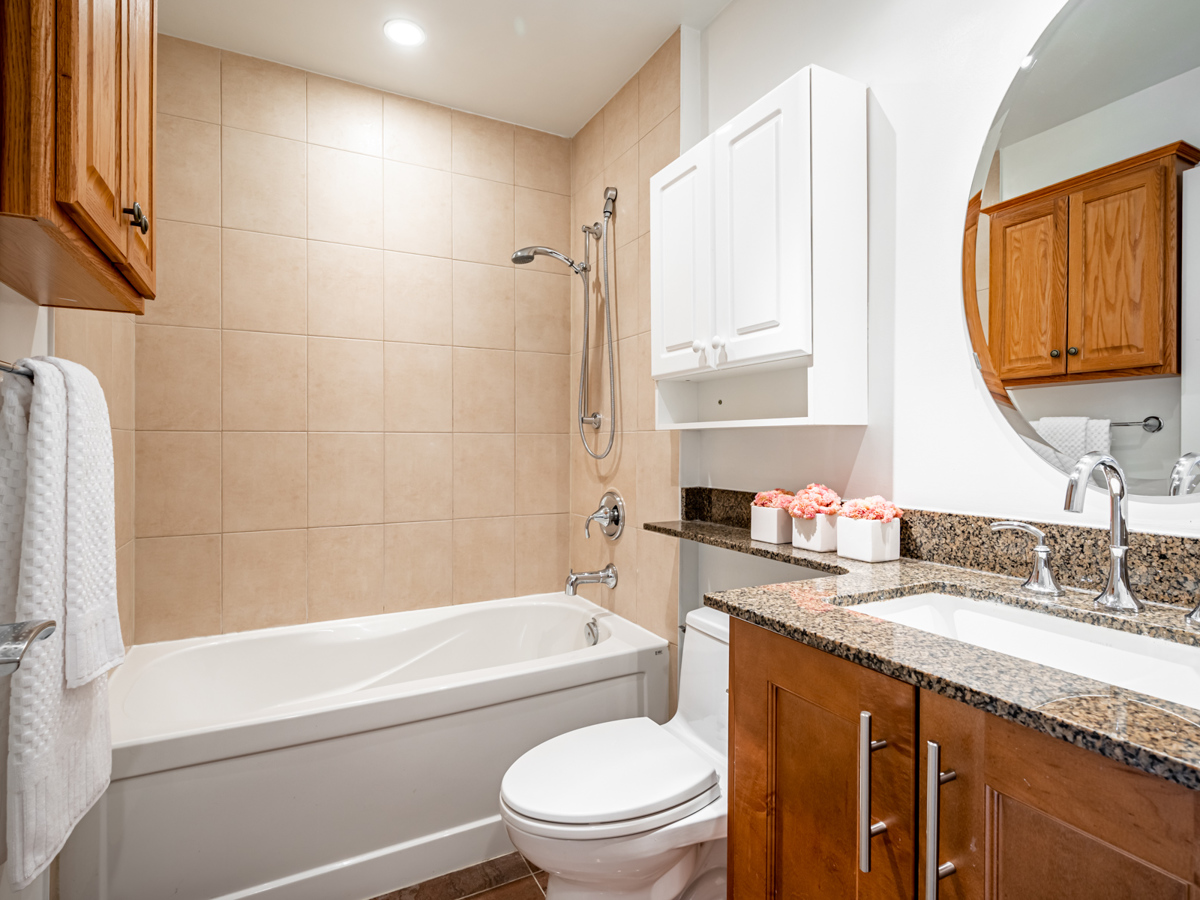 35 Balmuto St Unit 1407 – 4-piece bath with granite counters, soaker tub and multiple cabinets.