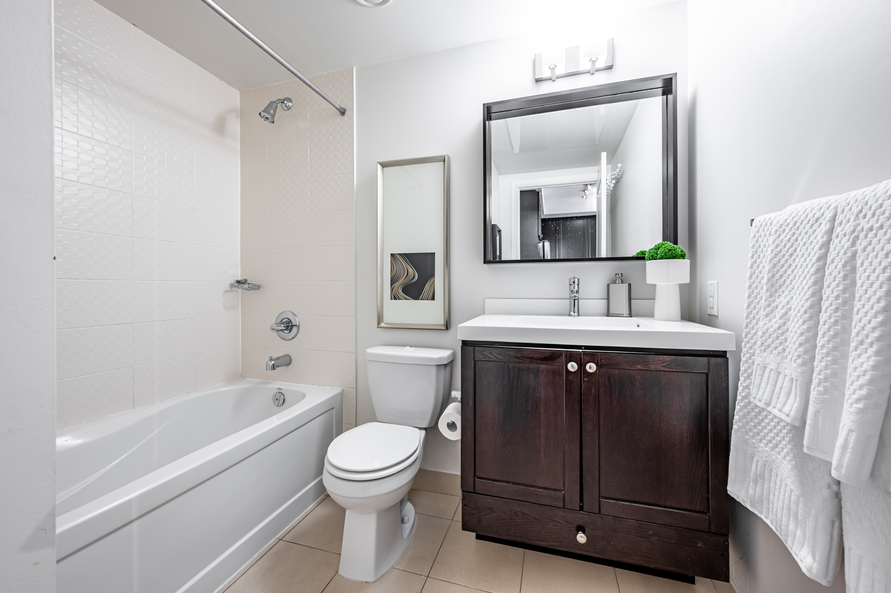 White condo bathroom with brown accents.
