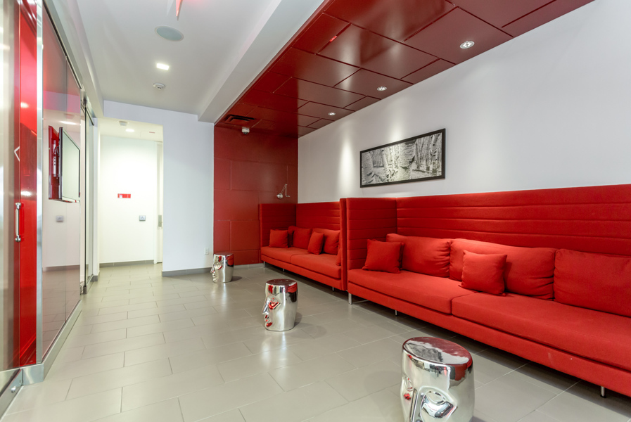 Reve Condos lounge with vibrant red seats and silver tables.