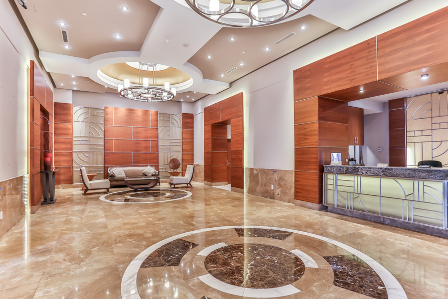 Sophisticated condo lobby with chandeliers, sleek tiles and wall designs.
