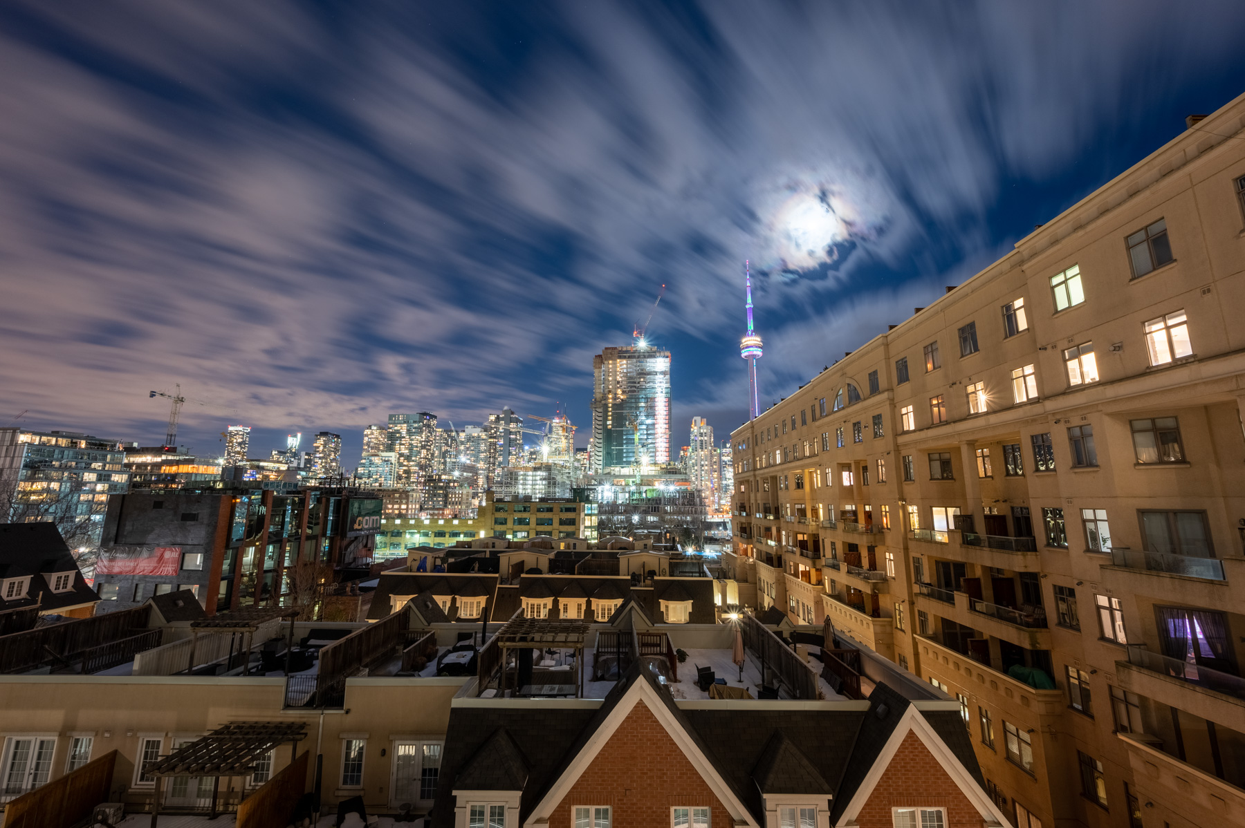 City lights, moonlit skies and blue lights of CN Tower in distance.