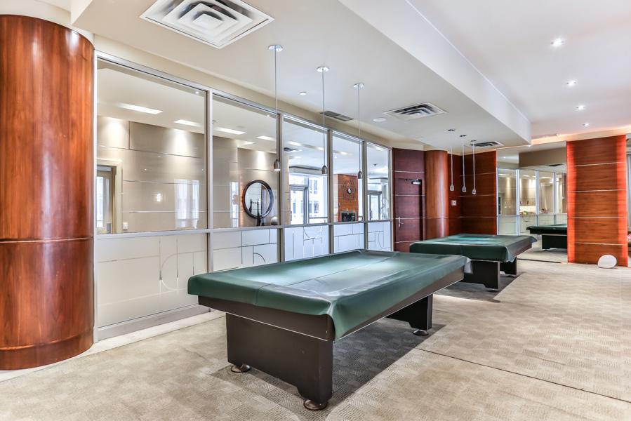 Empty condo rec centre with billiards tables.