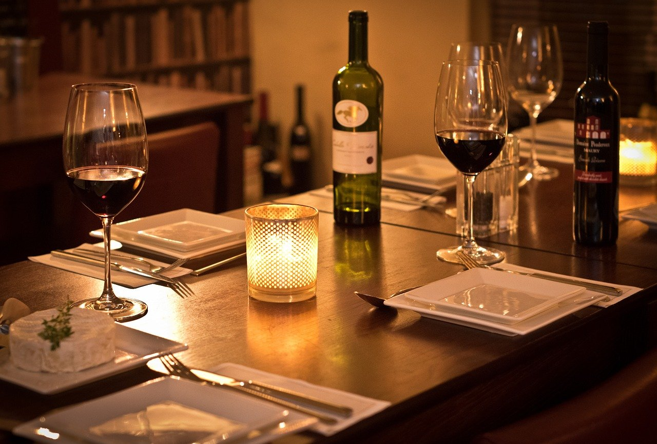 Dimly lit bistro with table, chairs, wine glasses and candles.