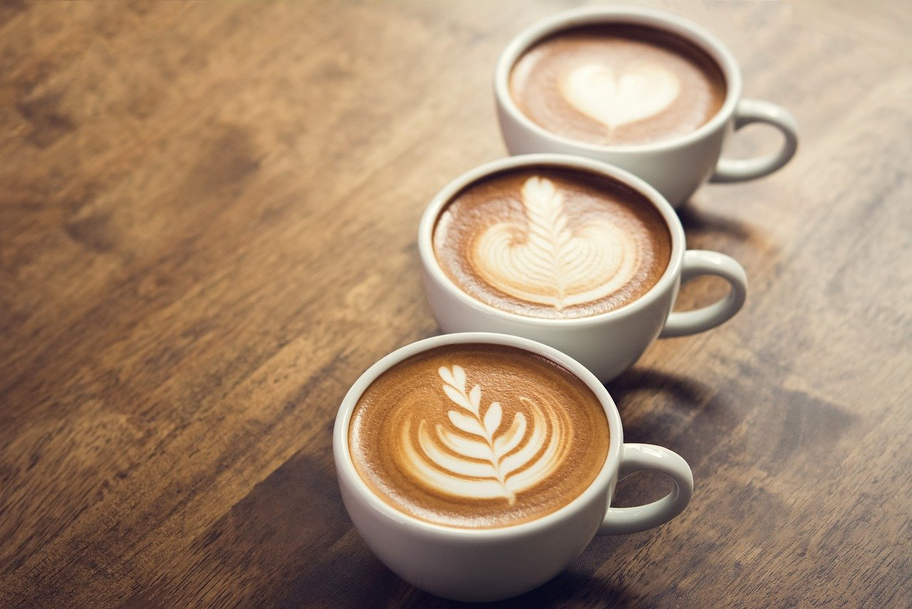 Three cups of espresso with fancy designs.