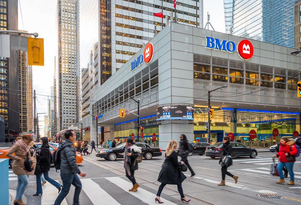 Pedestrians crossing street in foreground; BMO building in background.