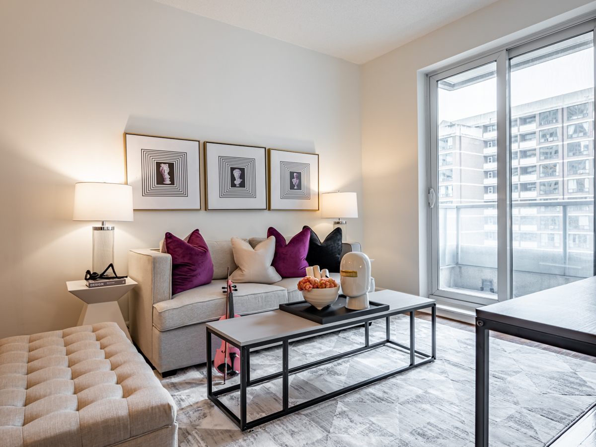 Condo living room with gray walls, gray sofa and purple pillows.