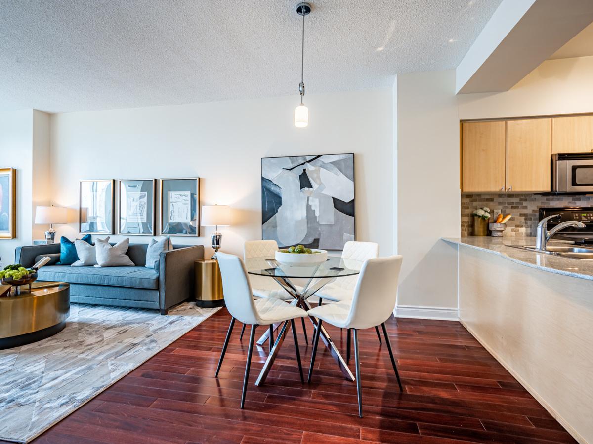 Condo with dark hardwood floors, brown door and light-coloured walls.