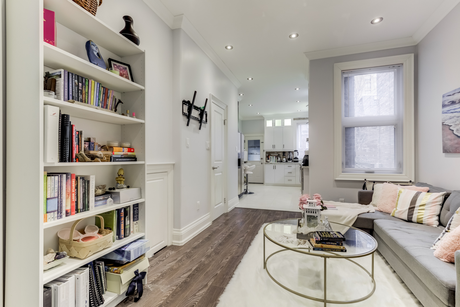 Living room with bookshelf showing upsizing to a house.