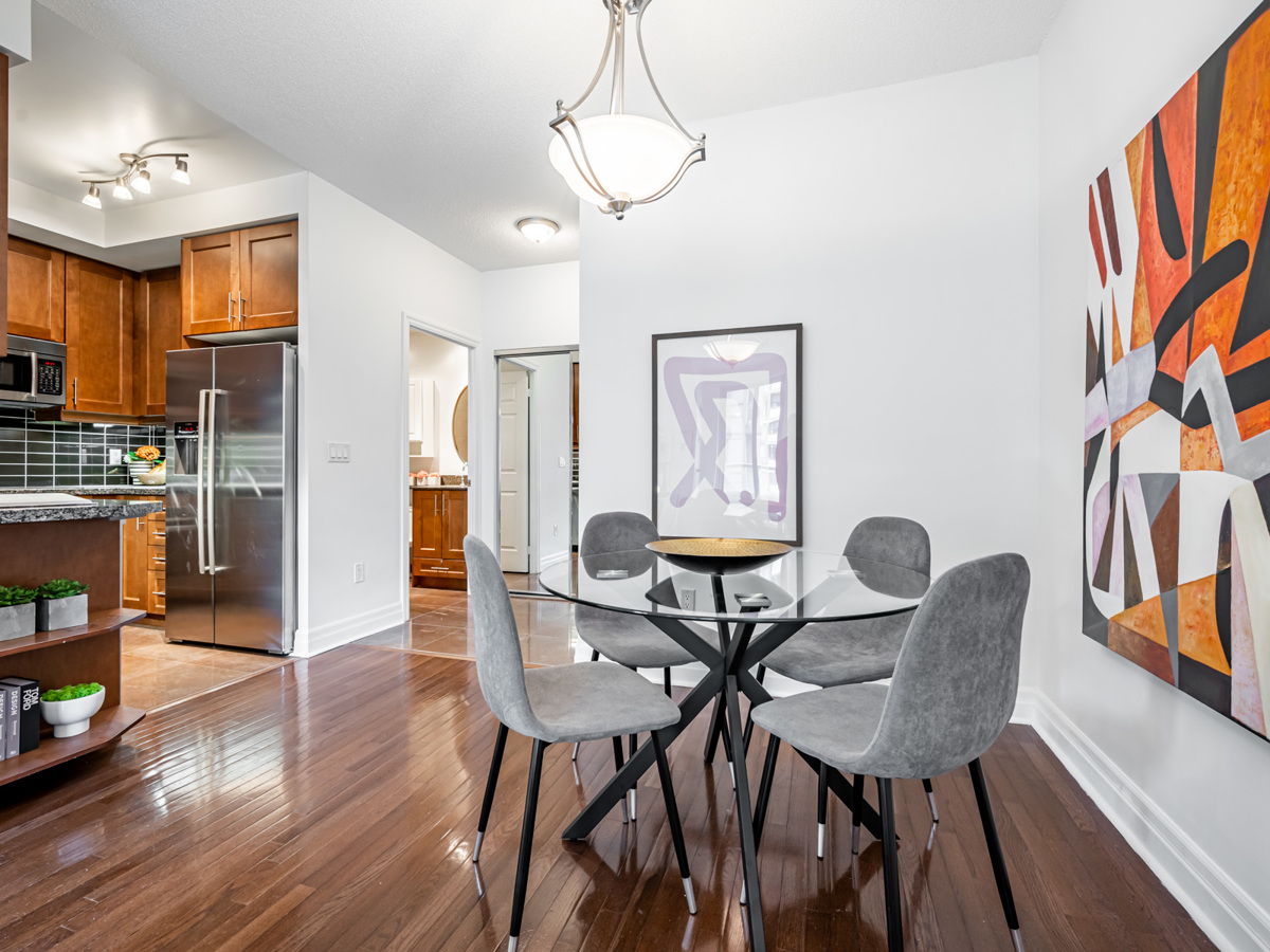 Condo dining room with elegant ceiling light overhanging dining table.