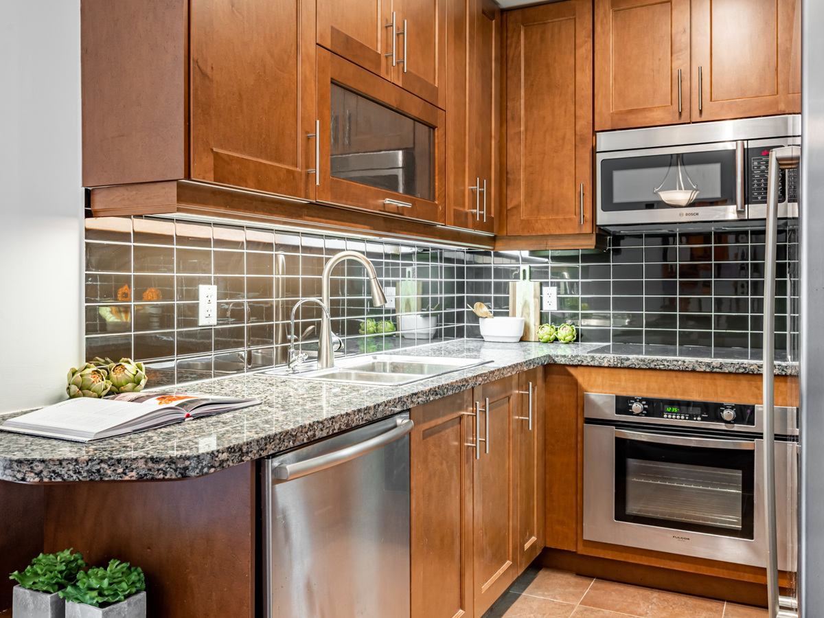 Beautiful condo kitchen with black granite counters, wood cabinets and black tiled back-splash.