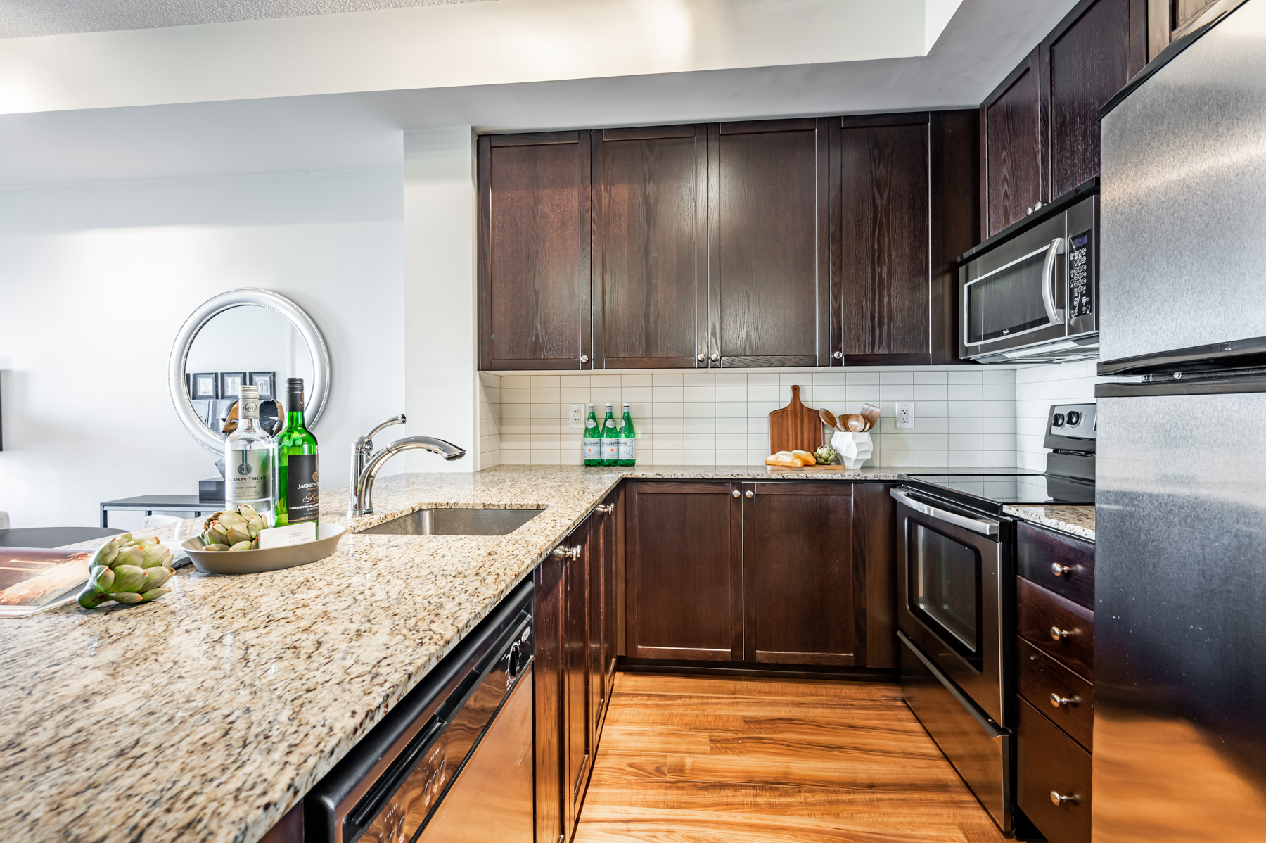 U-shaped condo kitchen with granite counters, dark wood cabinets and porcelain backsplash.