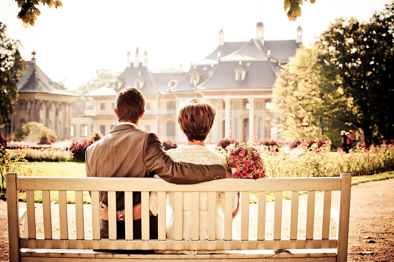 Married couple sitting on bench looking at house.