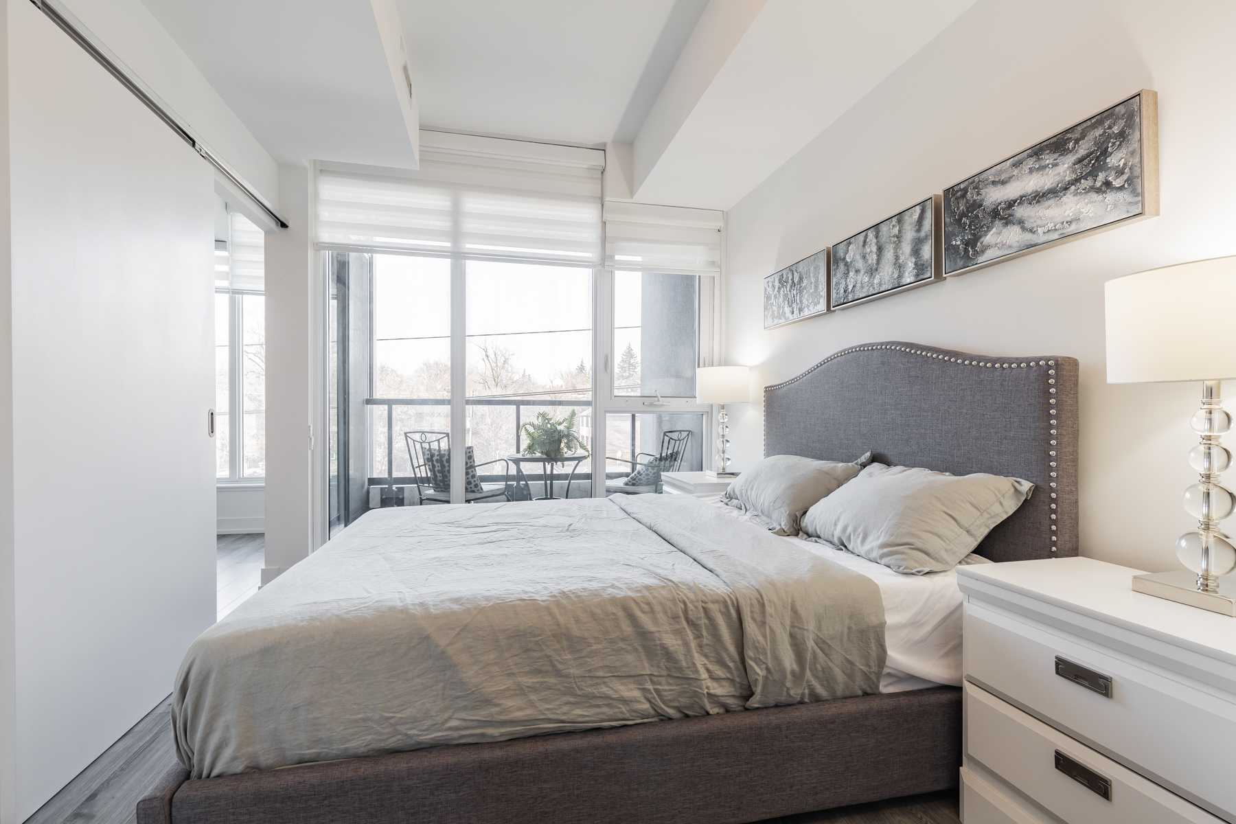 Brightly lit condo bedroom with bed overlooking balcony.