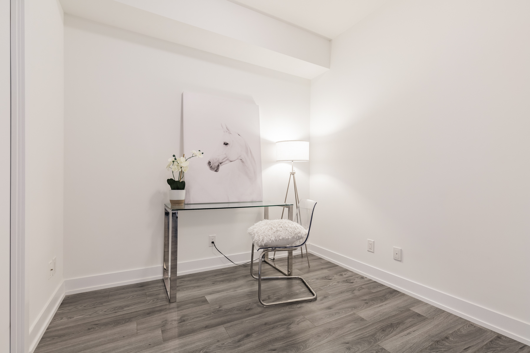 Condo den with desk, chair and horse painting.