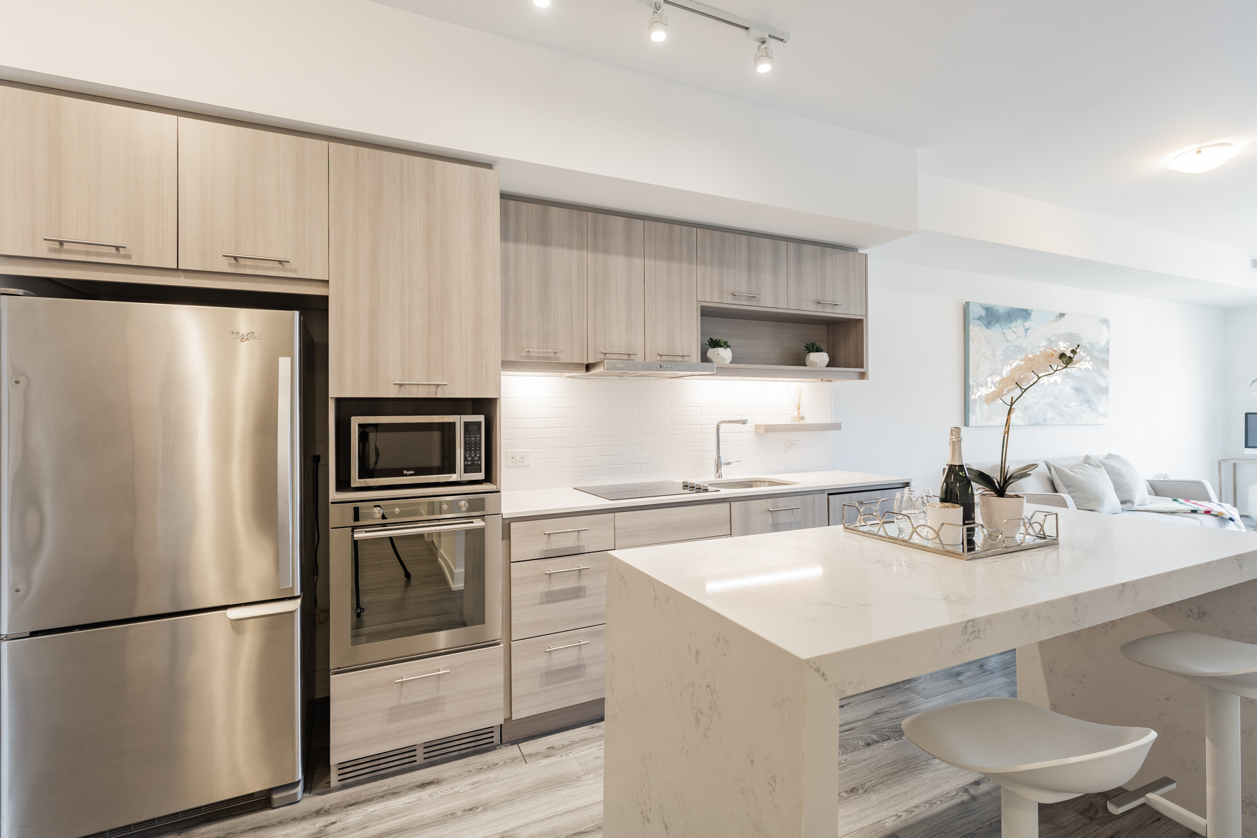 Contemporary condo kitchen with wood cabinets and white counters.