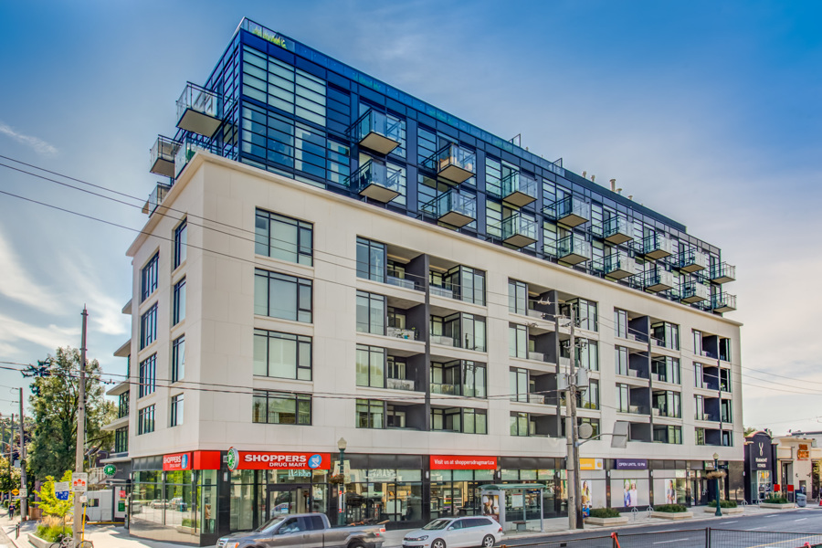 Exterior of The Hill Condos with shops at ground level.