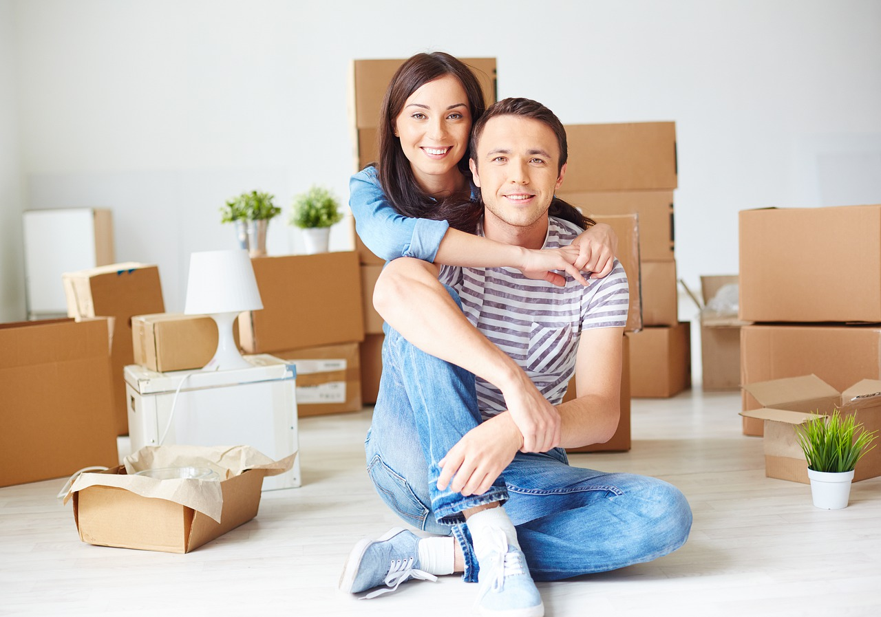 Young couple sitting on floor embracing with moving boxes in background.