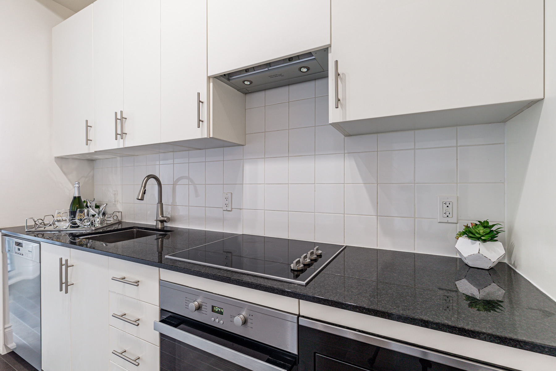 23 Glebe Rd W condo kitchen with white cabinets, black granite counters and white ceramic backsplash.