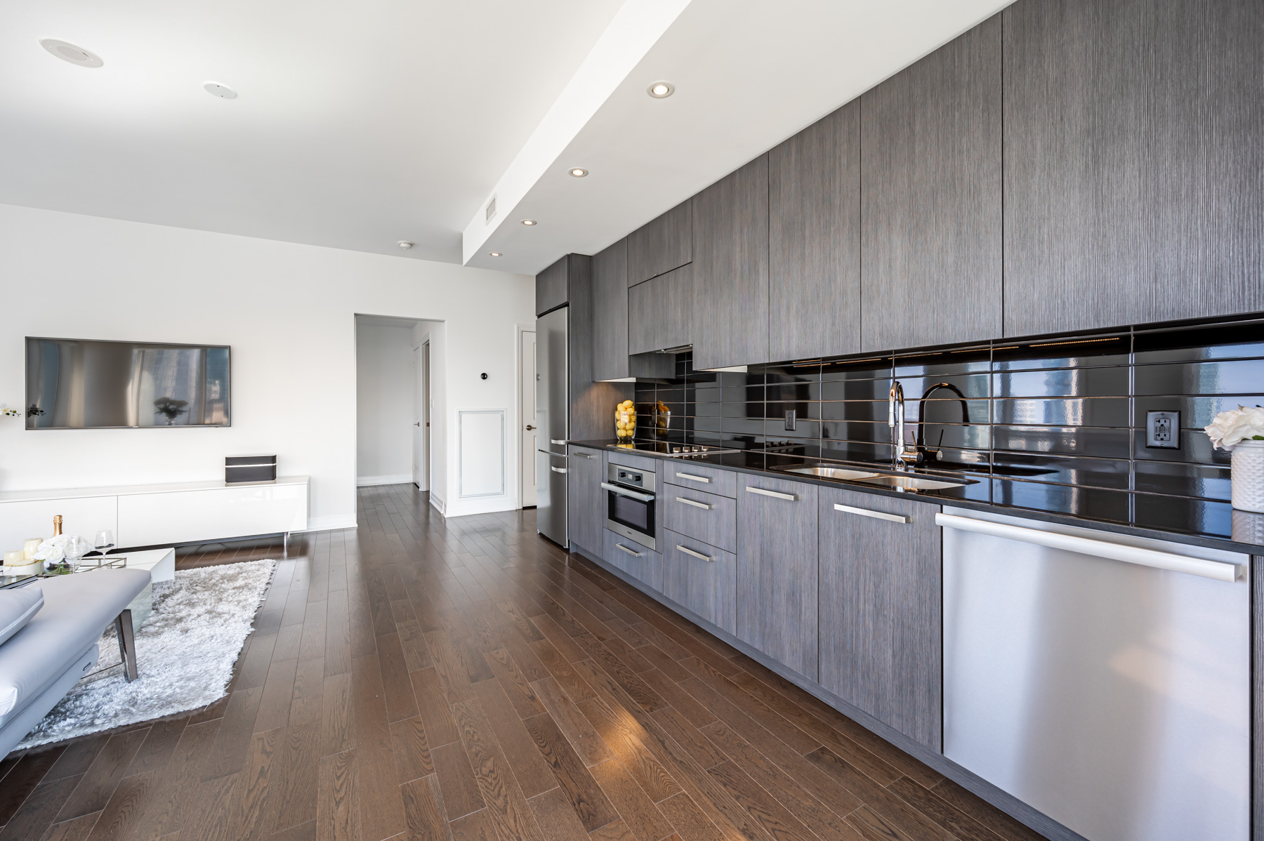 Long condo kitchen with several big cabinets and drawers.