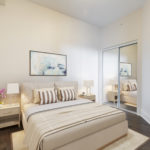 Large master bedroom with bed, 2 tables and paintings.