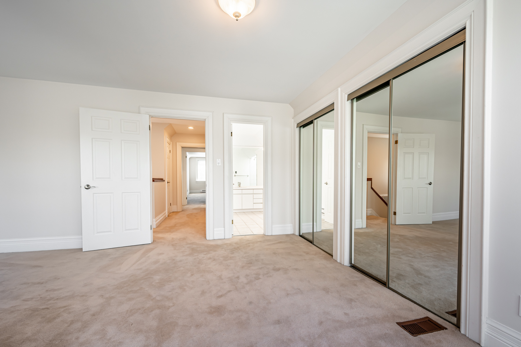 Bedroom with his and her closets with sliding mirror doors.