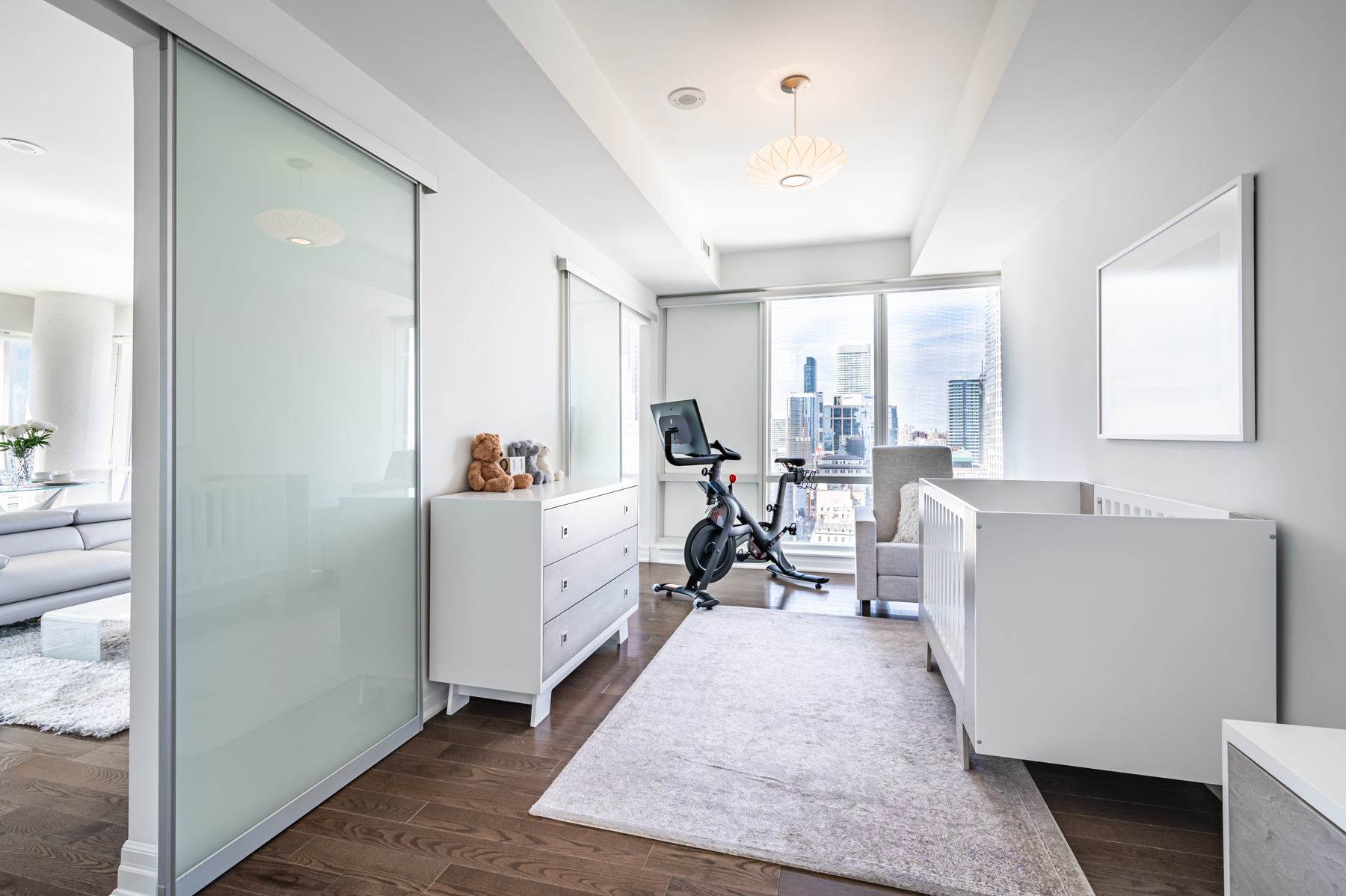 3305-8 The Esplanade Ave – second bedroom with crib, exercise bike and white furniture.