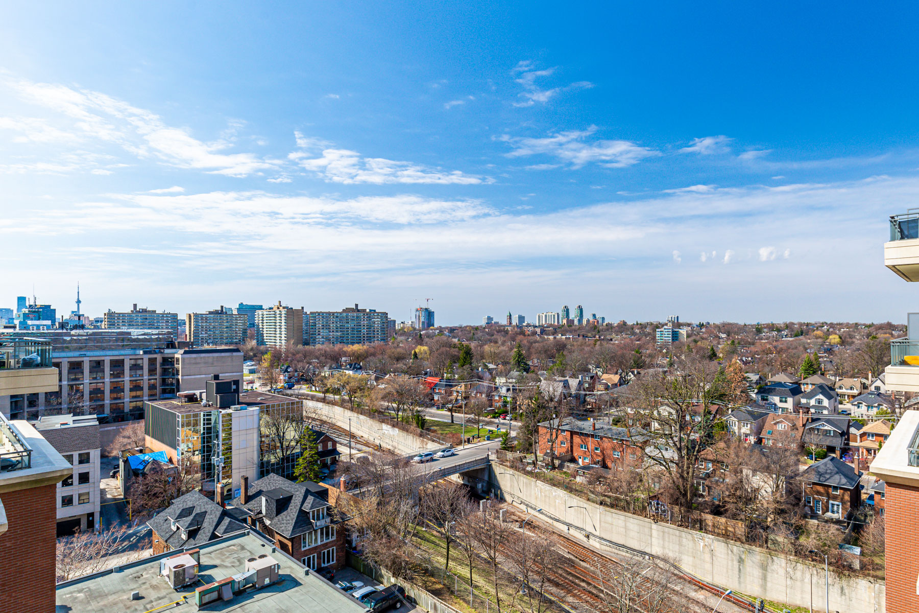 View of houses, buildings and trees of Midtown Toronto in foreground and downtown Toronto in background.