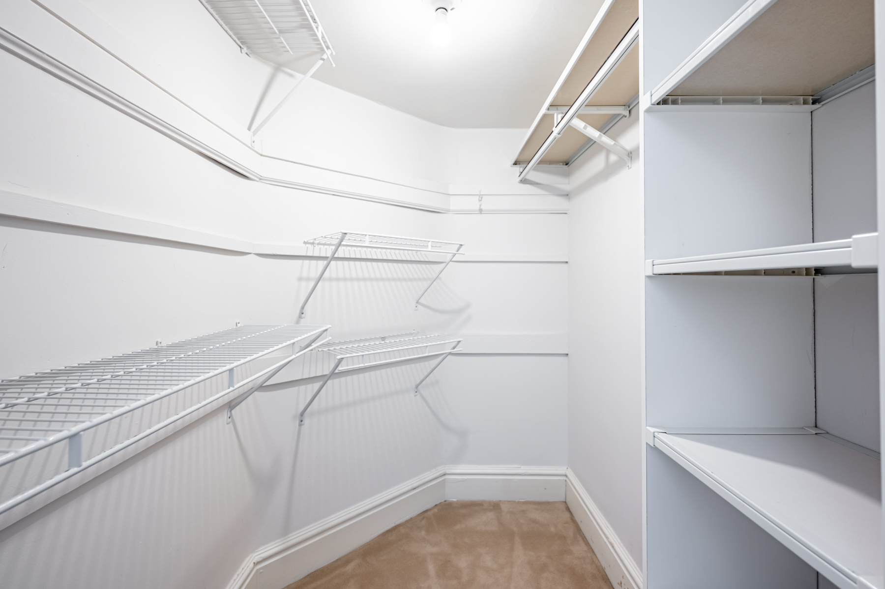 Walk-in closet with wire shelves and compartments.