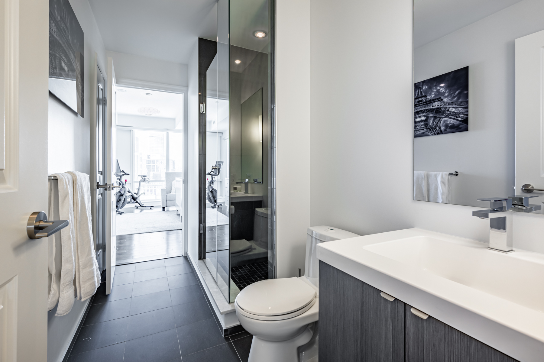 3-piece ensuite bath with dark tiles and glass shower.