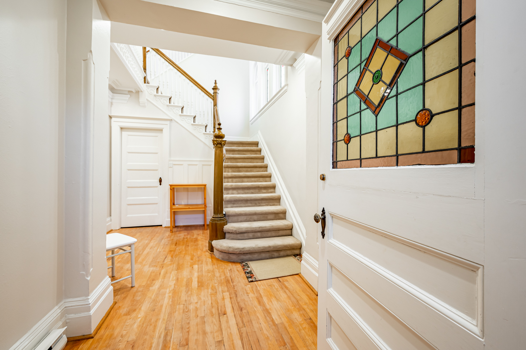 98 Bedford Rd foyer with hardwood floors, carpeted stairs and front door with stained glass inserts.