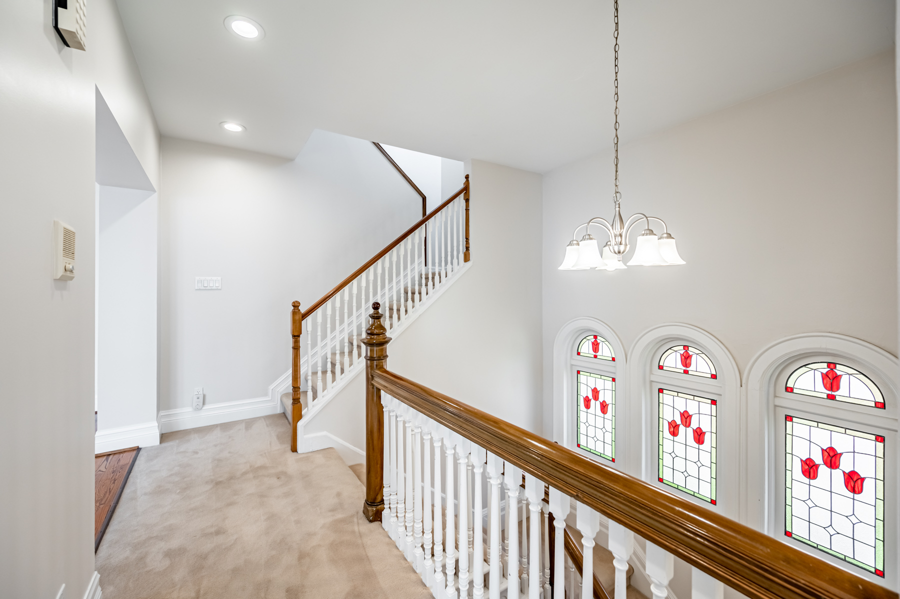 House stairway with shiny wood banisters, silver chandelier, pot-lights and stained glass windows.