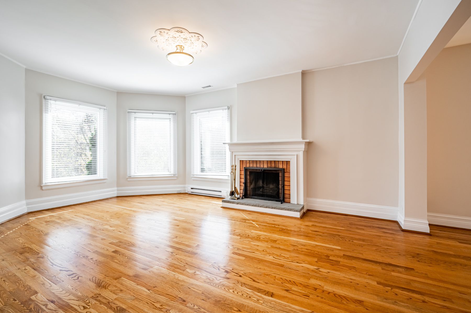 98 Bedford Rd living room with 3 large windows, ceiling lamp and fireplace.