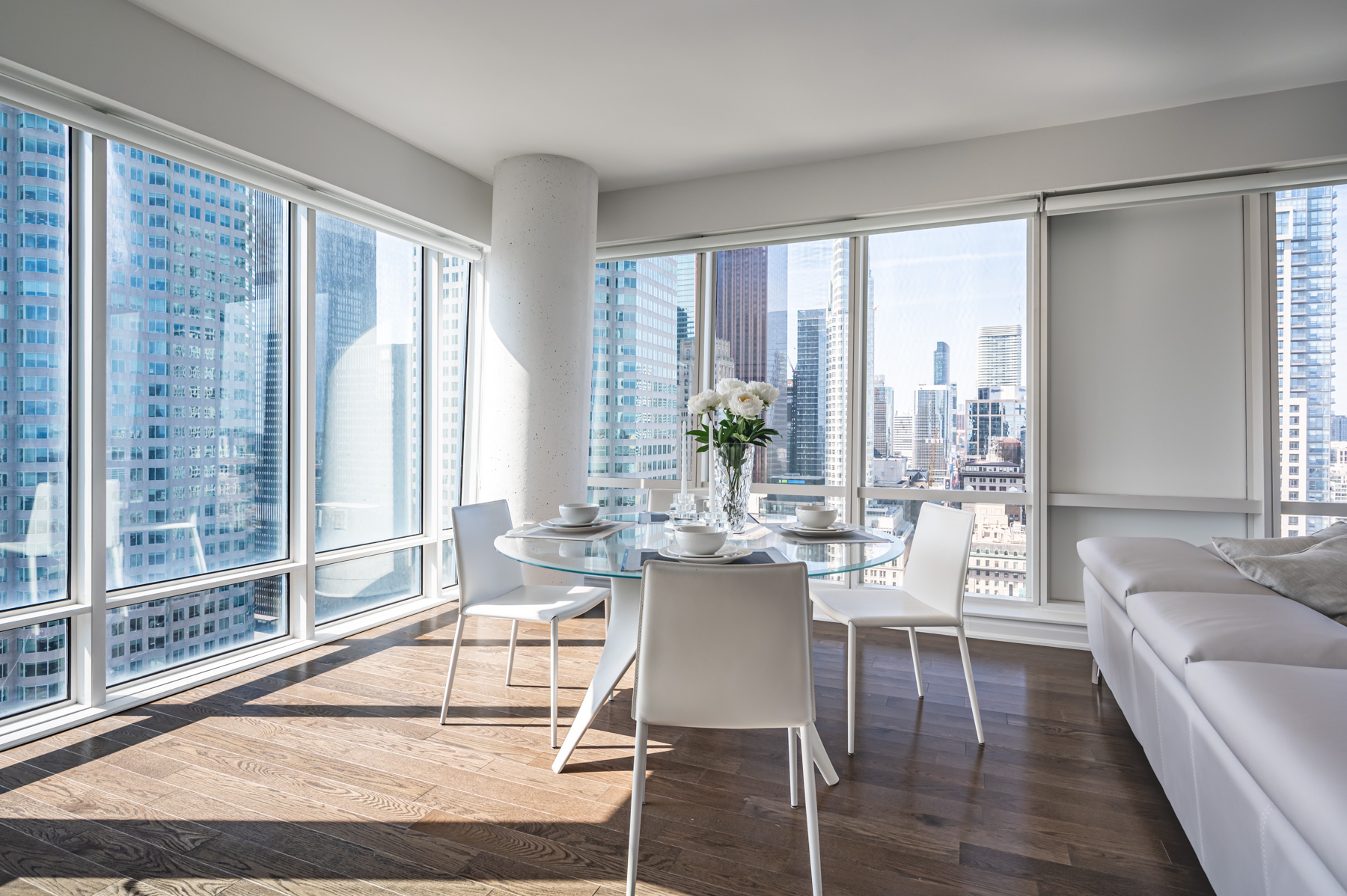 Condo dining room with view of Toronto through large windows.