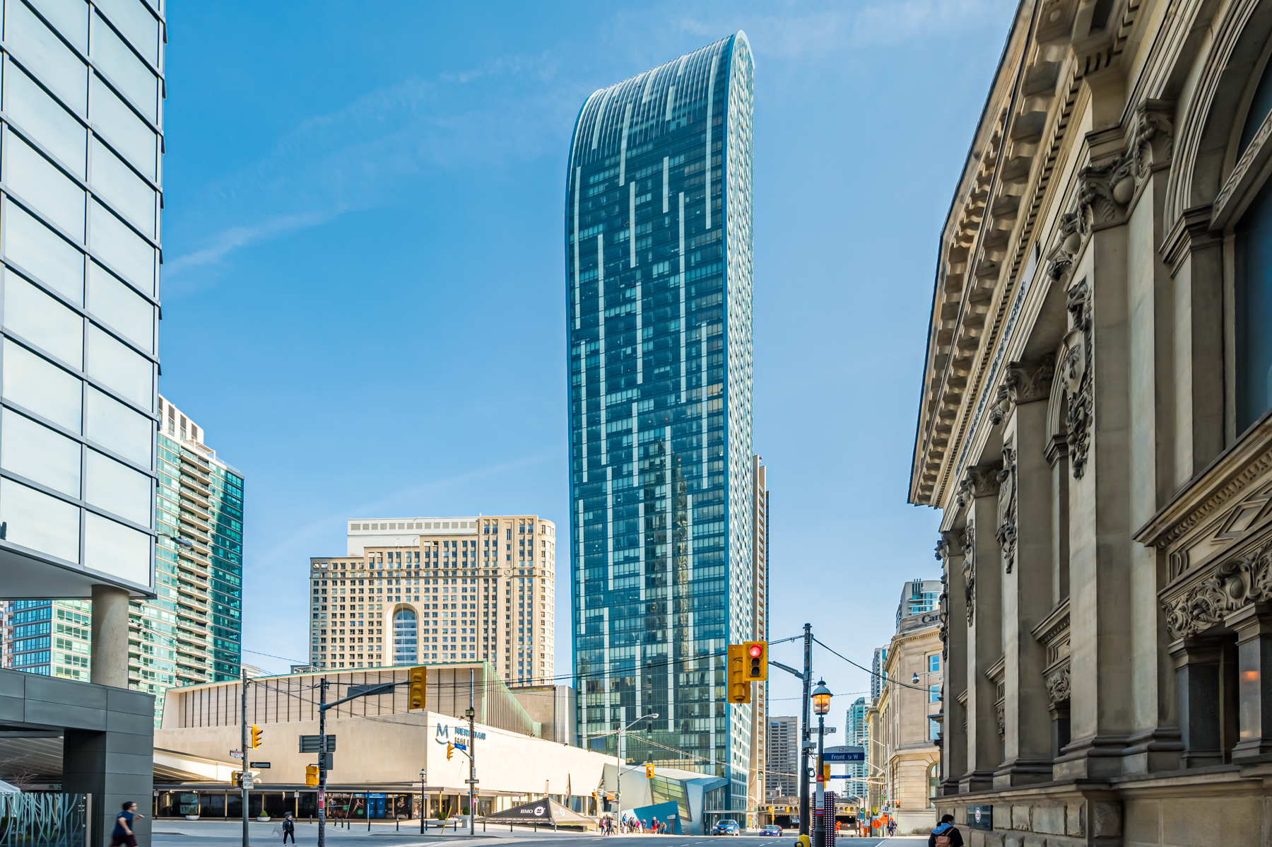Long distance photo of L Condos, a blue glass tower.