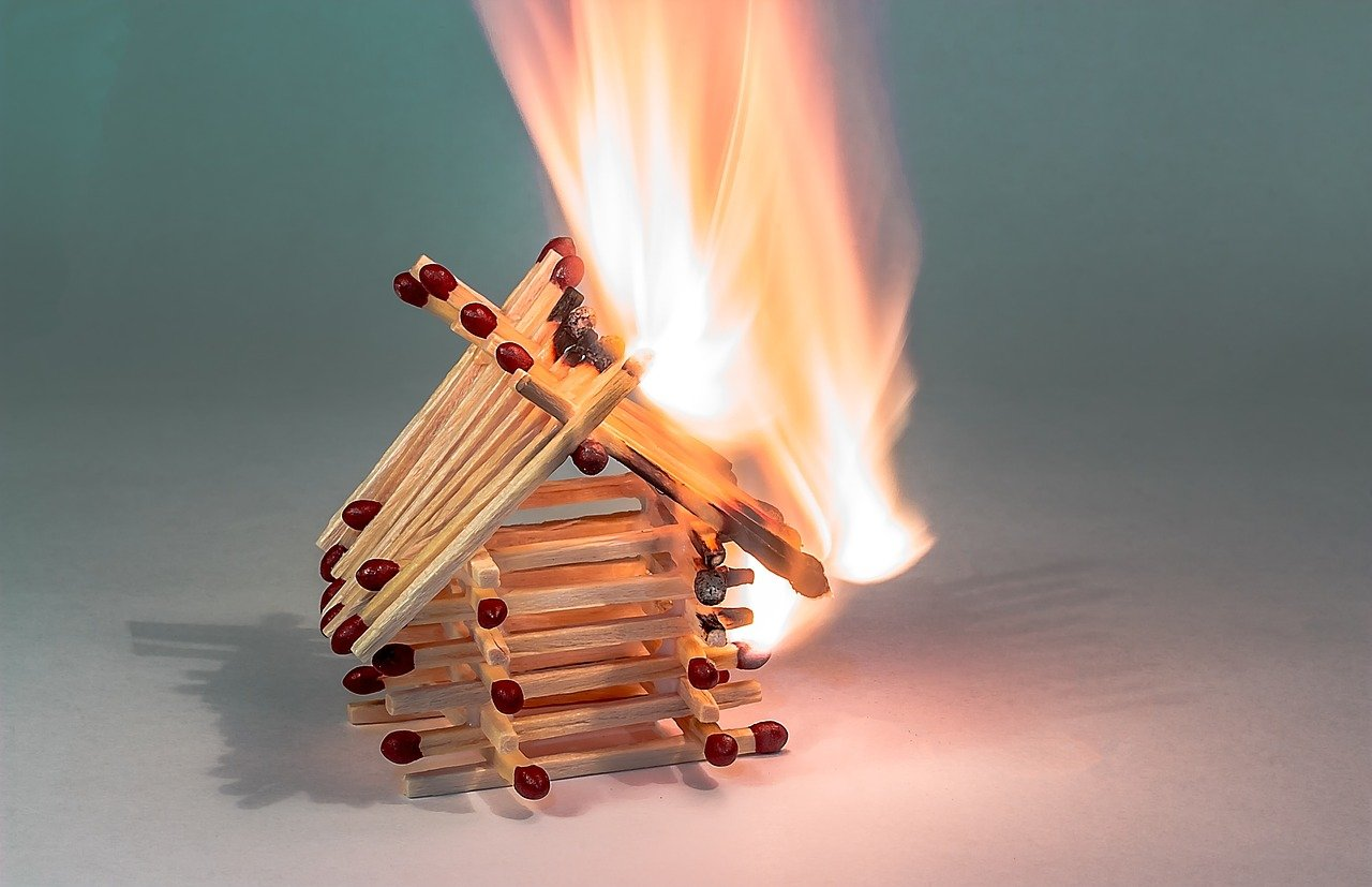 Matchstick house on fire showing heated March 2021 housing market.