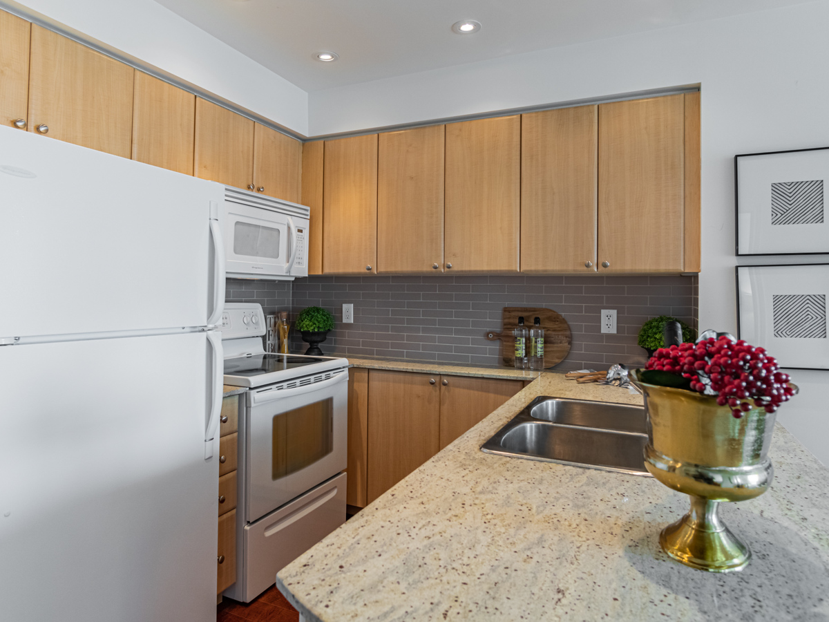 L-shaped condo kitchen with wood cabinets and drawers.
