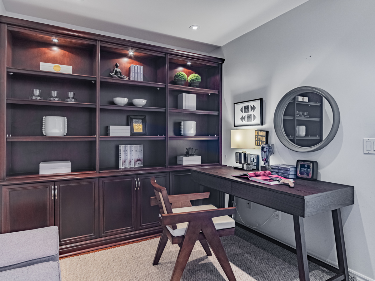 Condo den with built-in shelves and desk.