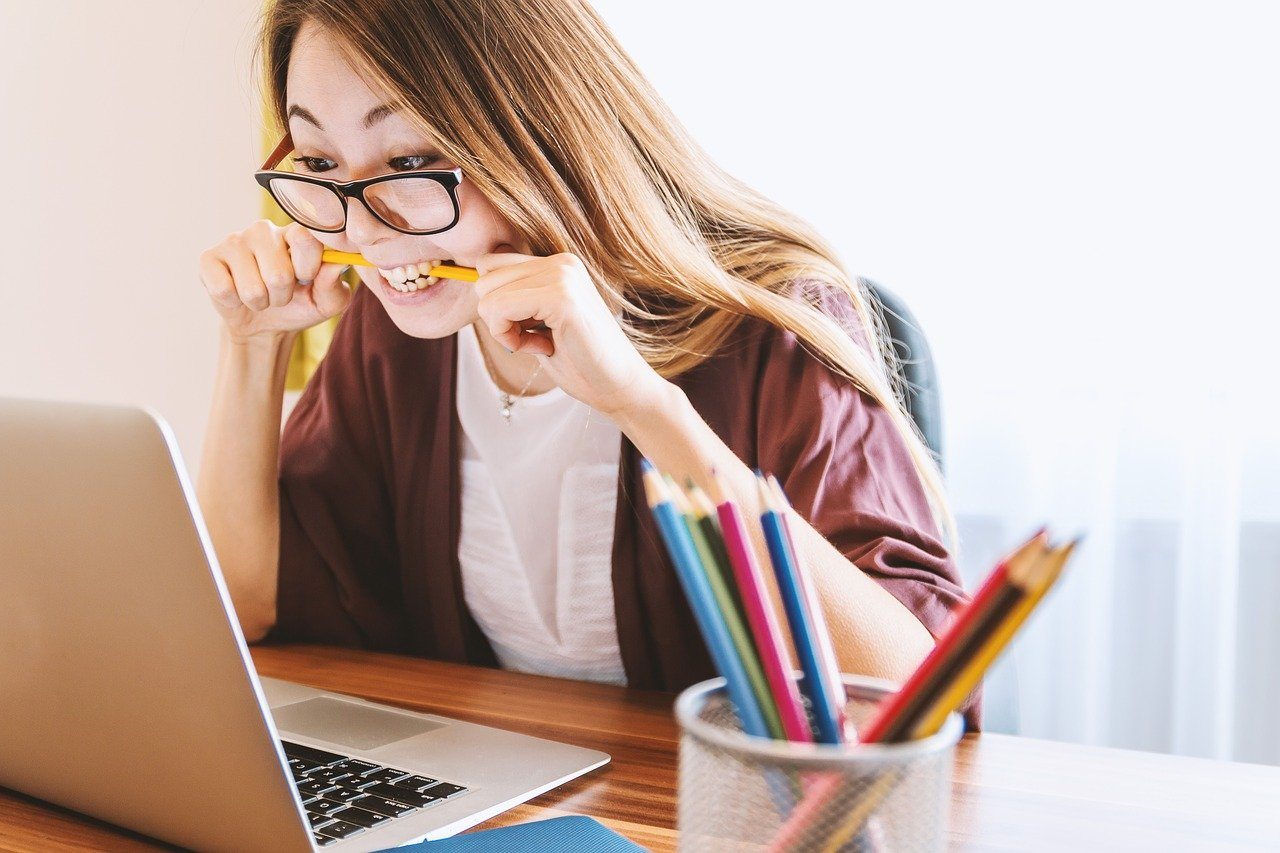 Young woman biting pencil to show anxiety over new mortgage stress test.