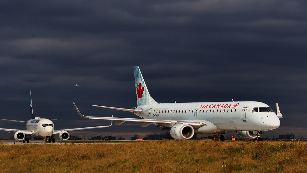 Air Canada plane on tarmac with dark skies above.