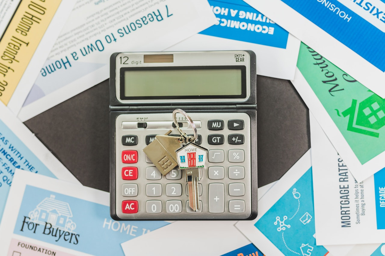 Calculator and house keychain showing rising prices from permanent residency programs.