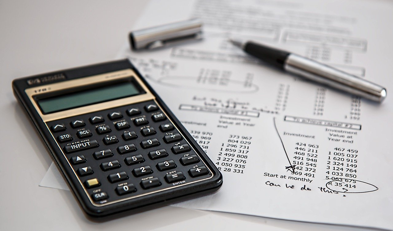 Calculator, pen and paper showing different tax rules for foreign investors.