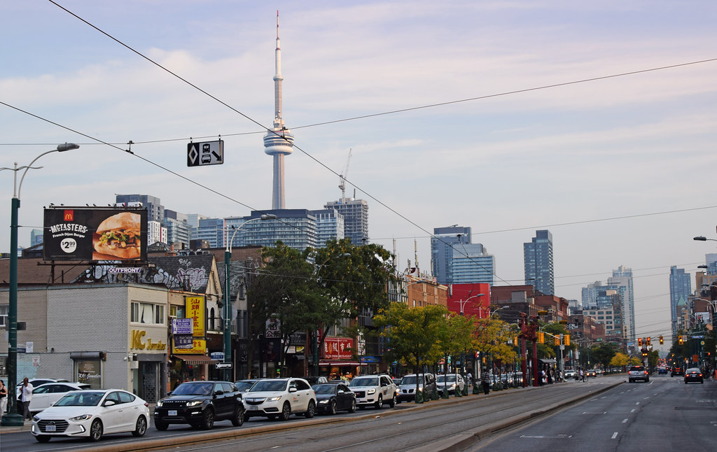 Traffic along Chinatown Toronto with CN Tower in background