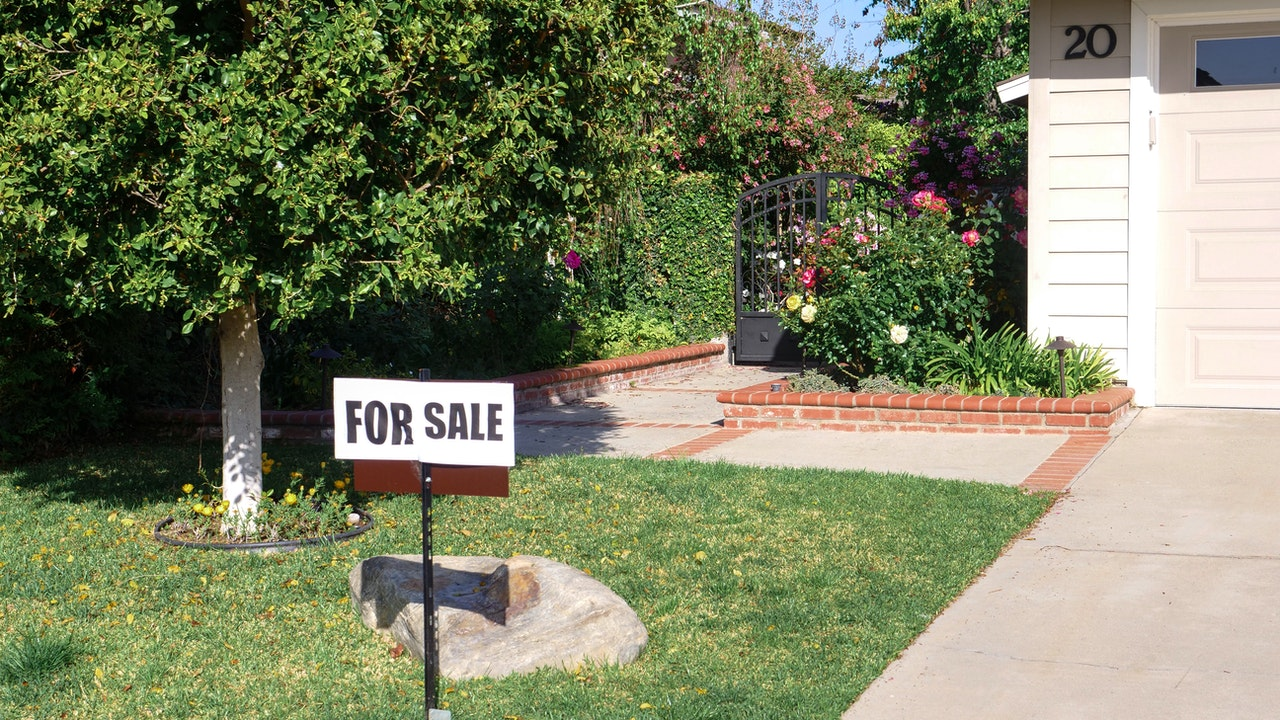 For sale sign on house lawn.