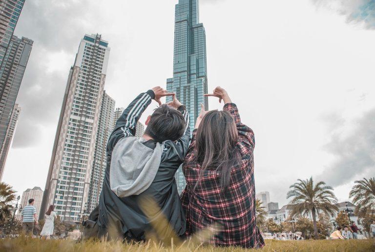 2 young Millennials looking up at condo.