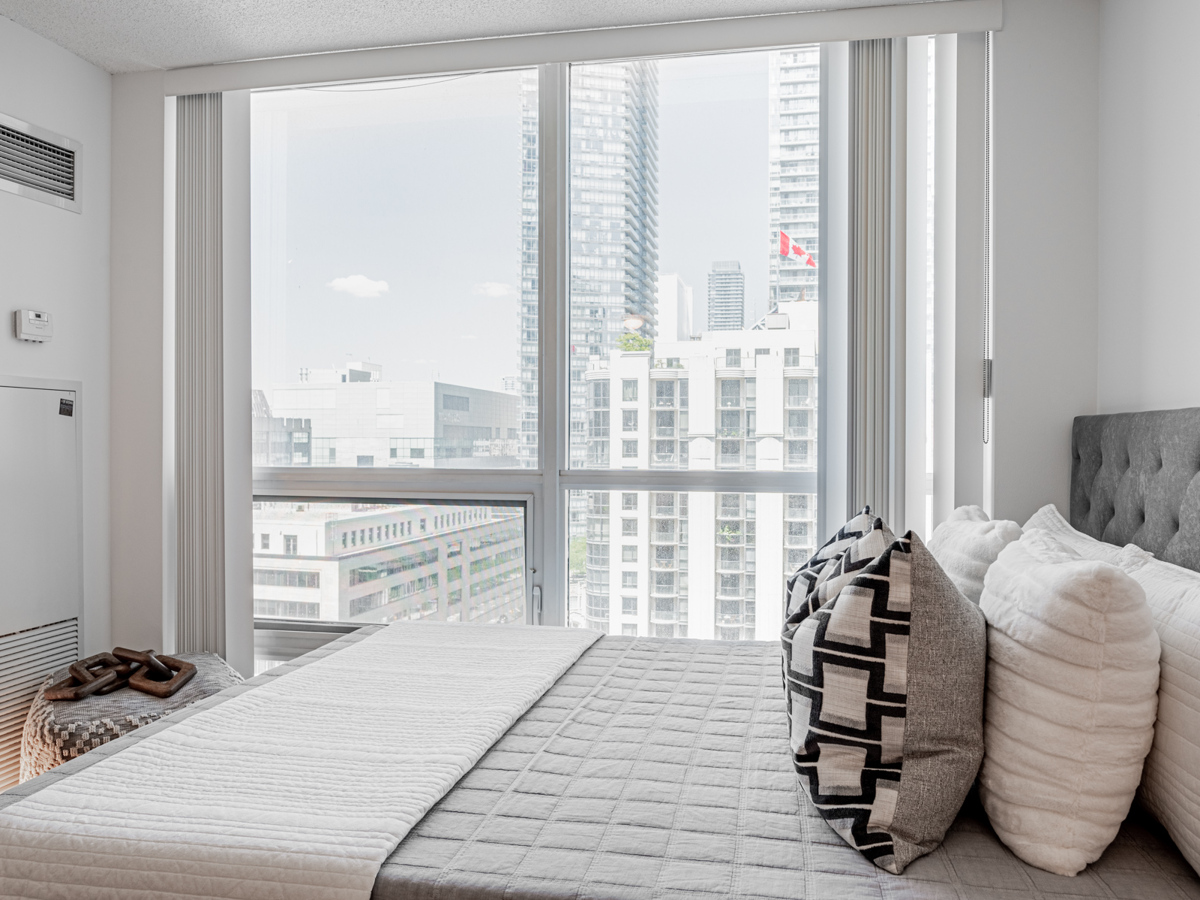 Condo bedroom with large windows showing buildings.