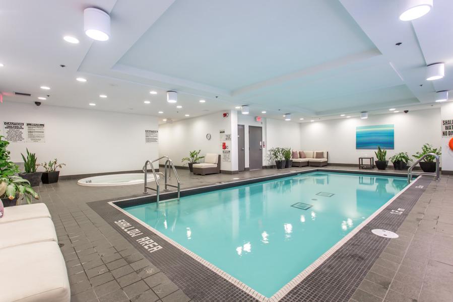 Empty condo swimming pool with greenish water.