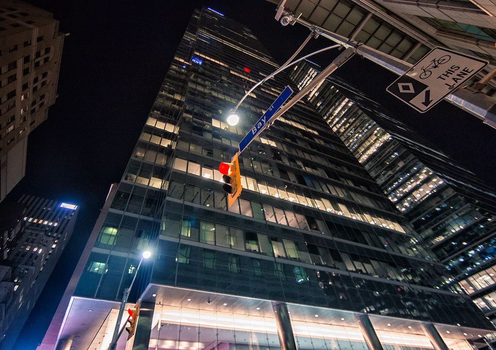 Looking up at building on Bay Street at night.