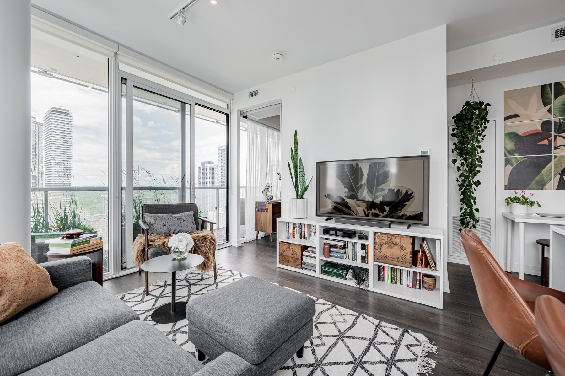 Condo living room with potted plants and dark laminate floors.