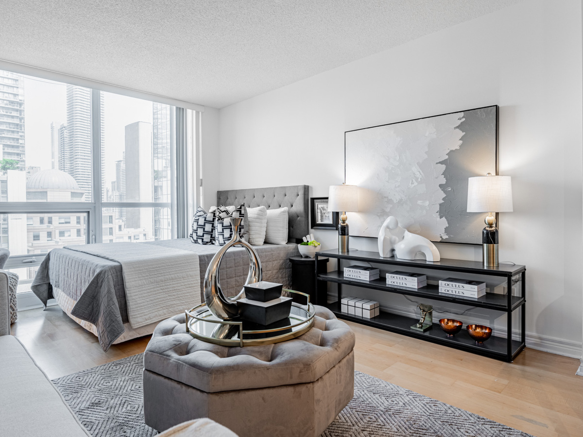 Condo living area lit by floor-to-ceiling windows.