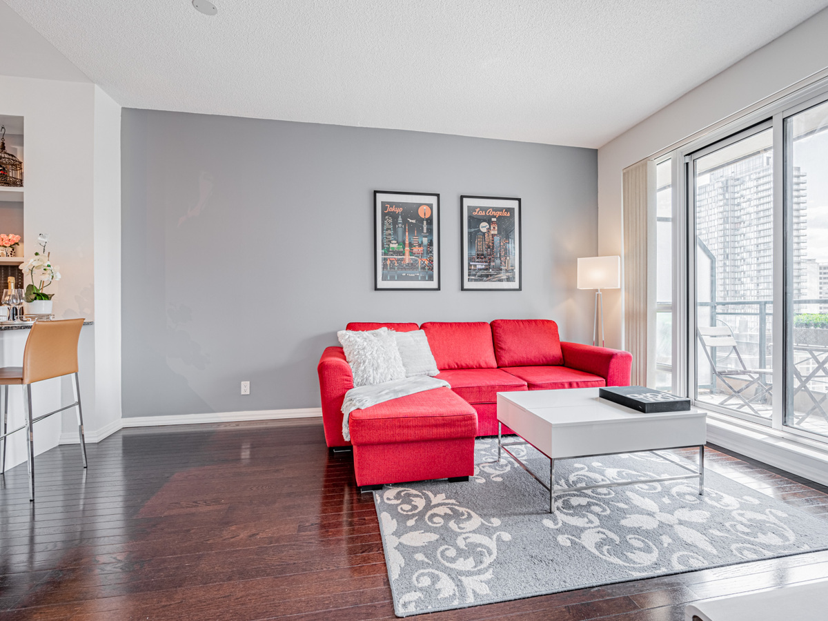 Condo living room with red sofa and empty space.